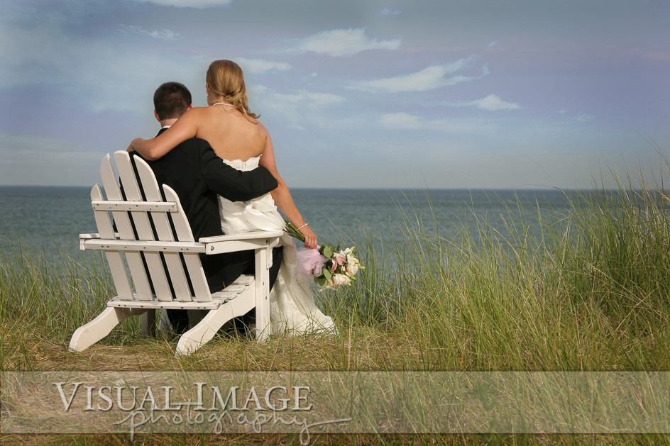 Bride sitting on groom's lap in adirondack chair at Blue Harbor Resort looking out at Lake Michigan