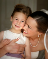 Bride wearing veil and pearl necklace looking at flower girl while hugging her