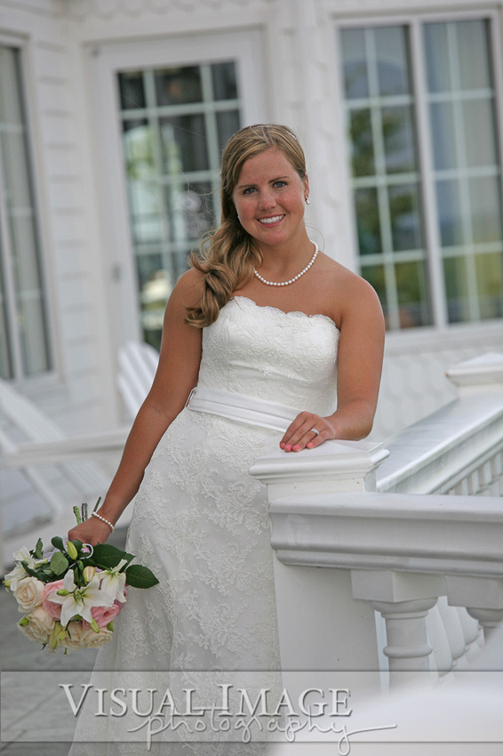 Bride leaning on railing at Blue Harbor Resort on her wedding day