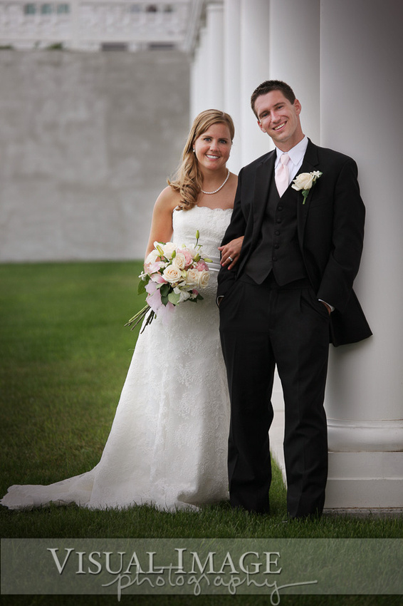 Bride and groom posing against white columns at Blue Harbor Resort on their wedding day